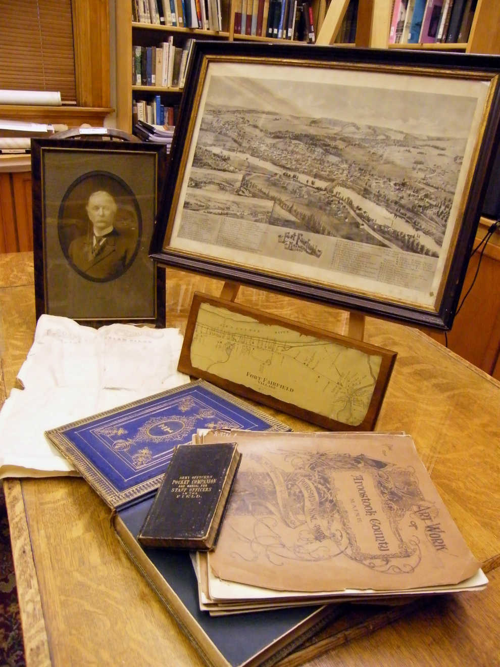 A photo of Colonel Franklin Drew with his Civil War field manual and historic maps and sketches of Fort Fairfield and the surrounding area. Photo courtesy of Fort Fairfield Public Library.