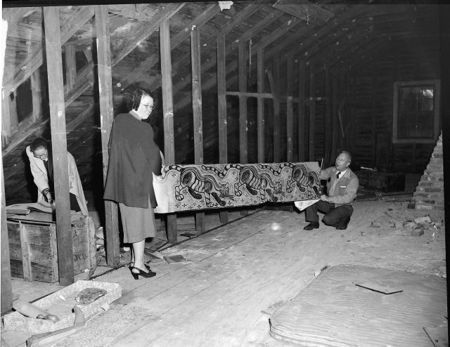 """Ray Thompson and Ruthe M. Carr hold a Walter Anderson print in the unfinshed attic at Oldfields House, a National Historic Site in Mississippi. Originally published in Down South Magazine, this photograph was one of the many saved with the assistance of NEH grants. Image courtesy of Mississippi Gulf Coast Community College C.C. """"Tex"""" Hamill Down South Magazine Collection."""