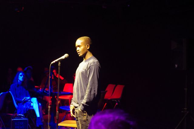 A participant in the project's Storylab workshop shares his migration story publicly at a local Story Slam. Image courtesy of the Kansas African Studies Center at the University of Kansas.