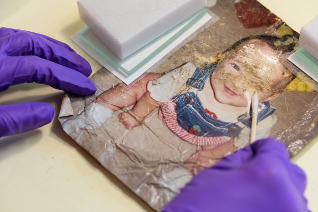 Jacklyn Chi, a first-year Master's student in the Winterthur/University of Delaware Program in Art Conservation removes embedded dirt and grime using a dry cotton swab from a family photograph salvaged from the Wimberley, Texas floods. Image courtesy of Evan Krape, the University of Delaware.